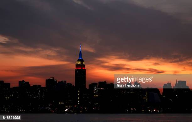 The Empire State Building stays lit in its September 11 colors as the sun rises in New York City on September 12 2017 as seen from Hoboken New Jersey