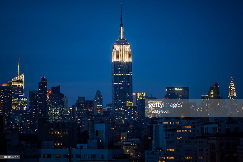 CONTENT] The Empire State Building still stands tall in the NYC skyline. The building is lit in white at the top this night. Chrysler Building appears on the right of the image.