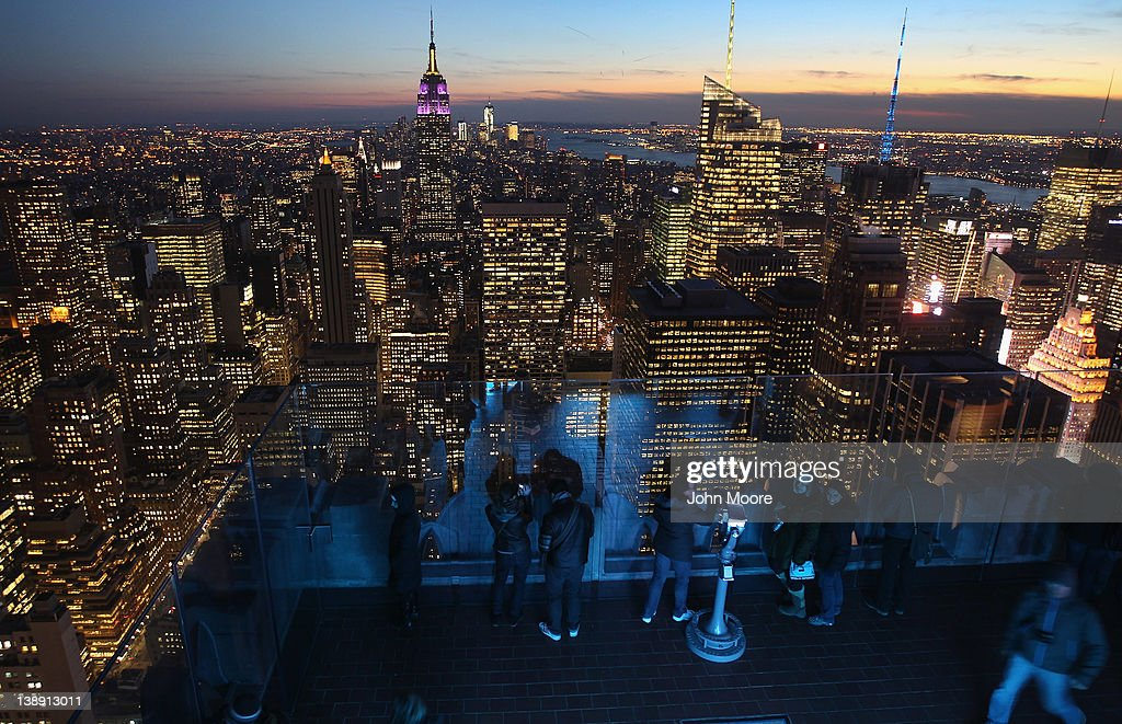 The Empire State Building towers over the Manhattan skyline as tourists gather on the observation deck of Rockefeller Center on February 13, 2012 in New York City. The owner of the Empire State Building, Malkin Holdings, plans to raise up to $1 billion in an initial public offering on the 102 story Manhattan landmark.