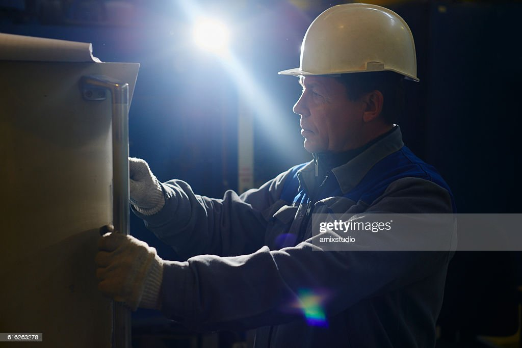 The employee clicks on the control panel of the equipment : Stock Photo