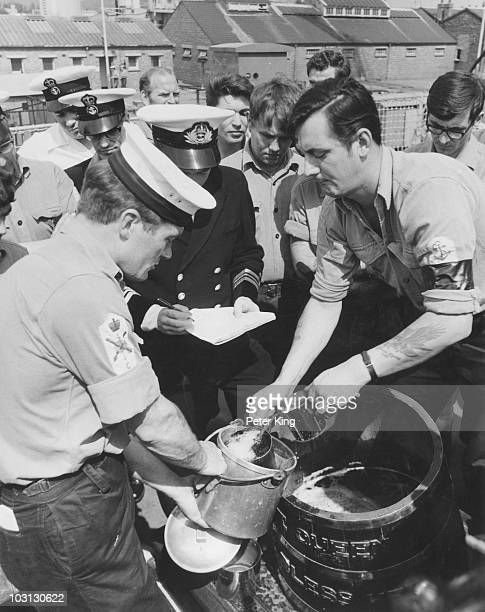The end of a Royal Navy tradition as the daily ration of rum is abolished due to safety concerns 31st July 1970 LSA Michael Johns issues rum to the...