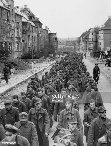 The endless procession of German prisoners captured with the fall of Aachen marching through the ruined city streets to captivity October 1944