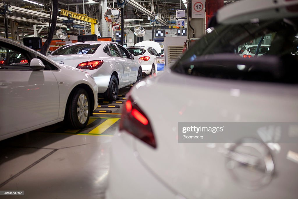 The engines and light systems of white Opel Astra automobile are operated at the end of the production line at General Motors Co's Adam Opel AG...