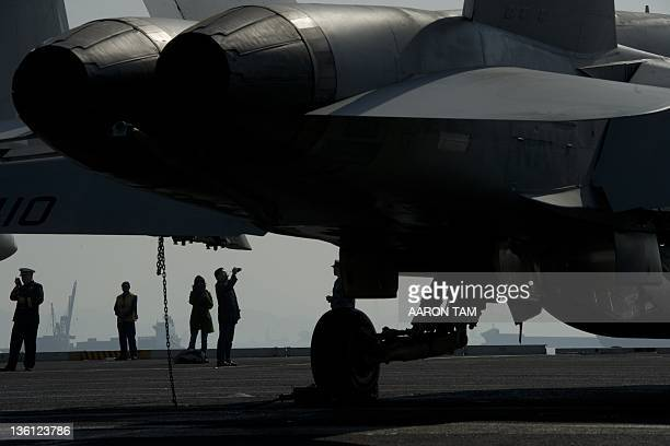 The engines of an F/A18 Hornet warplane is seen in the foreground with people in the background standing on the flight deck of the USS Carl Vinson a...