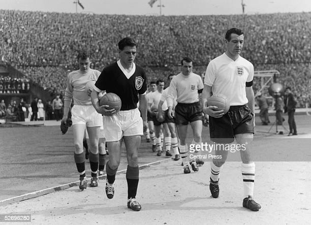 The England and Scotland captains Norman Haynes and Eric Caldow respectively lead their teams onto the pitch at Wembley at the start of the...