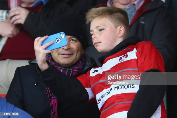 The England Rugby head coach Eddie Jones poses for a selfie with a young Gloucester supporter at half time during the Aviva Premiership match between...