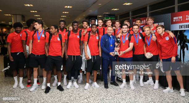 The England U20's squad and manager Paul Simpson pose with the World Cup after their arrival back at Birmingham Airport