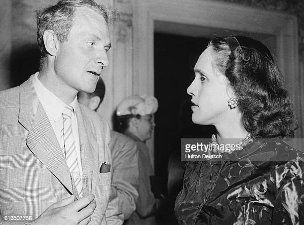 The English poet and critic Sir Stephen Spender talks to his wife at a party ca 1950