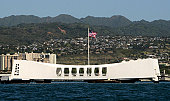 January 13, 2010, Pearl Harbor - The Ensign flies over the USS Arizona Memorial as Sailors from Naval Station Pearl Harbor prepare to repaint and beautify the brow and deck.