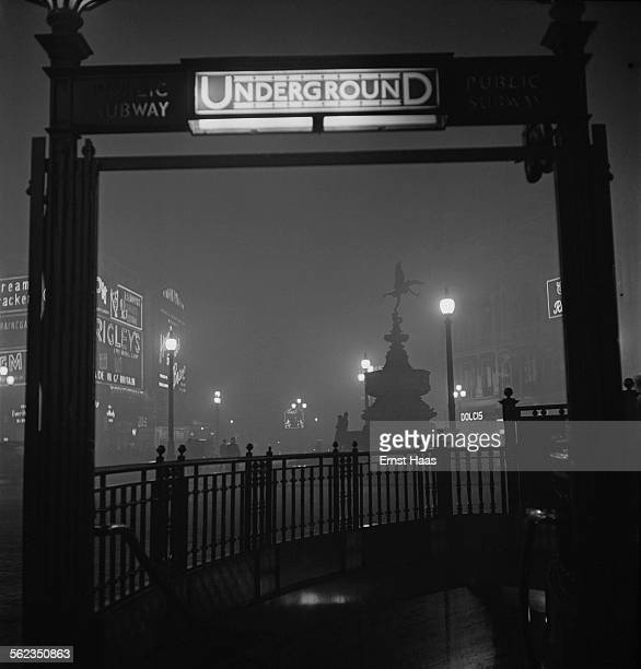 The entrance to Piccadilly Circus tube station at night London circa 1953