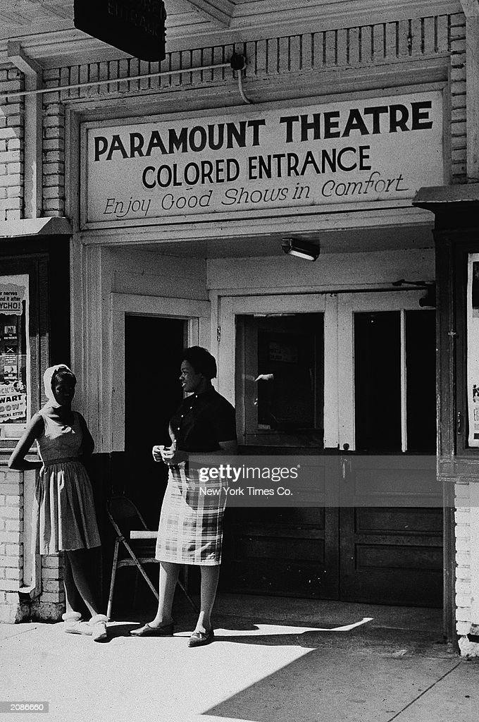 The entrance to the Paramount Theater showing a sign reading 'Colored Entrance' circa 1950