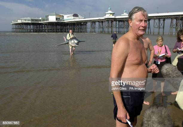 The Environment Minister Michael Meacher talks to the media as he leaves the water following a swim pursued by a man dressed as a shark protesting...
