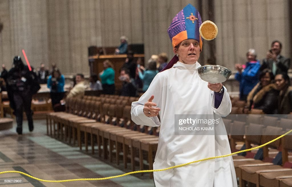 The Episcopalian Bishop of Washington Mariann Edgar Budde flips a pancake during the Shrove Tuesday Pancake Race at the National Cathedral in Washington, DC, on February 9, 2016. Shrove Tuesday, also known as Mardi Gras, precedes Ash Wednesday, the first day of Lent. / AFP / Nicholas Kamm