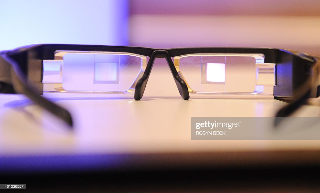 The Epson Moverio BT-200 smart glasses are seen at the 2014 International CES in Las Vegas, Nevada, January 7, 2014. The Moverio BT-200 projects two identical 16:9 images onto the lens-based screens, generating a semi-transparent picture to fall within the user's field of vision. The Android 4.0-based headset with portable controller features a front-facing camera and motion sensors for Augmented Reality and gaming. The glasses can be pre-ordered in the US now for USD $699 and are expected to ship in the spring. AFP PHOTO / Robyn Beck