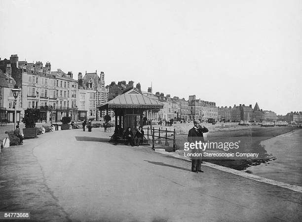 The esplanade at Weymouth Dorset circa 1900 Bathing machines can be seen on the beach in the background