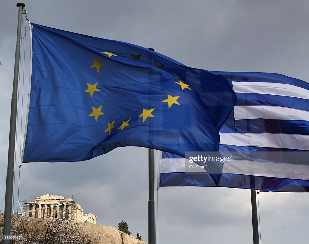 The EU and Greek flags fly in front of the Parthenon on the Acropolis on February 17 2012 in Athens Greece Following a meeting on Wednesday finance...
