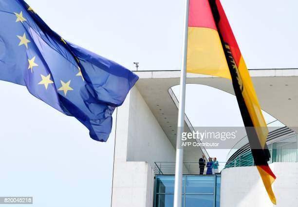 The EU and the German flag flutter as Britain's Prince William Duke of Cambridge and his wife Kate the Duchess of Cambridge are seen on the terrace...