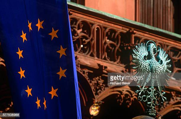 The EU flag hangs limply alongside the old German world Prussian eagle near the balcony of Frankfurt's Rathaus or Town hall in historic Romerberg...