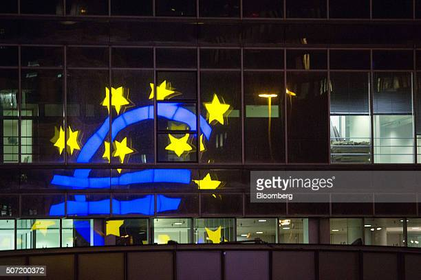 The euro sign sculpture is reflected in office windows as it stands outside the former European Central Bank headquarters at night in Frankfurt...