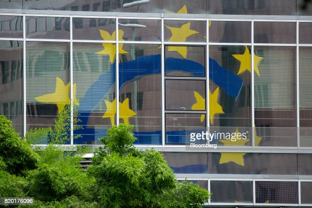 The euro sign sculpture sits reflected on a building window in Frankfurt Germany on Thursday July 20 2017 Frankfurt has emerged as a winner of the...