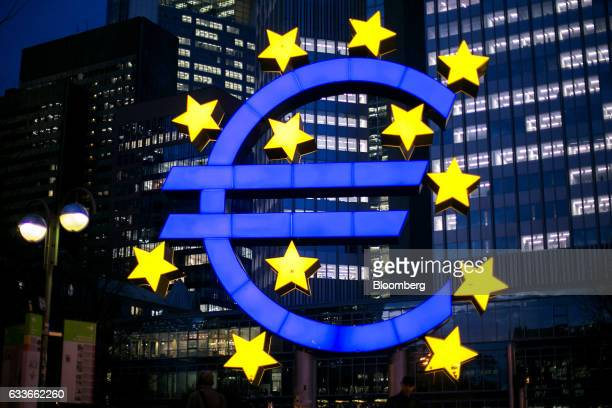 The euro sign sculpture stands illuminated near the former European Central Bank headquarters at dusk in Frankfurt Germany on Thursday Feb 2 2017...