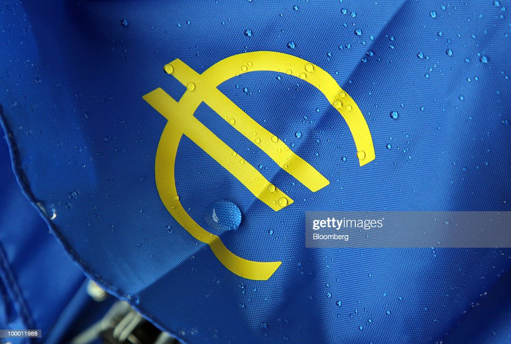 The European Central Bank (ECB) logo, featuring a euro symbol, is seen on a wet umbrella in Frankfurt, Germany, on Thursday, May, 20, 2010. Europe's debt crisis will depress the euro still further after it declined to the lowest level since 2006, according to UBS AG and BNP Paribas SA. Photographer: Hannelore Foerster/Bloomberg via Getty Images