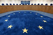 The European flag is pictured of the floor of a hearing room prior to the hearing regarding the complaint of a young French Muslim womans challenging...