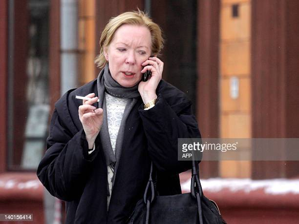 The European Union's ambassador to Belarus Maira Mora speaks by cell phone as she leaves the French embassy in Minsk on February 29 after her meeting...