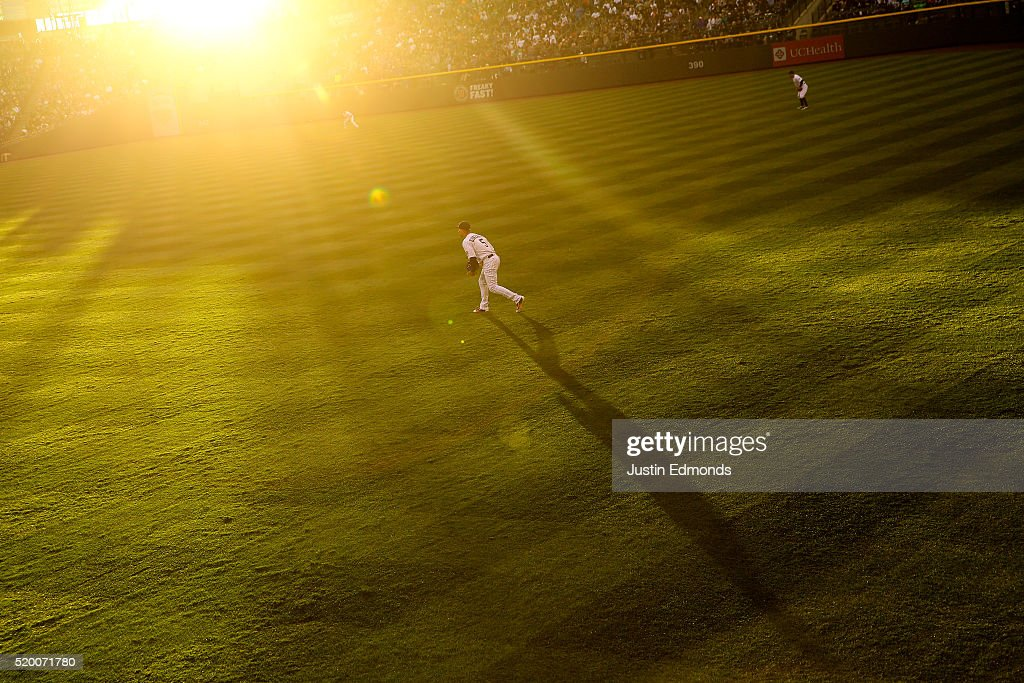 The evening sun glows as right fielder Carlos Gonzalez #5 of the Colorado Rockies prepares for the pitch during the third inning against the San Diego Padres at Coors Field on April 9, 2016 in Denver, Colorado.