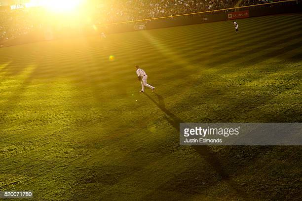 The evening sun glows as right fielder Carlos Gonzalez of the Colorado Rockies prepares for the pitch during the third inning against the San Diego...