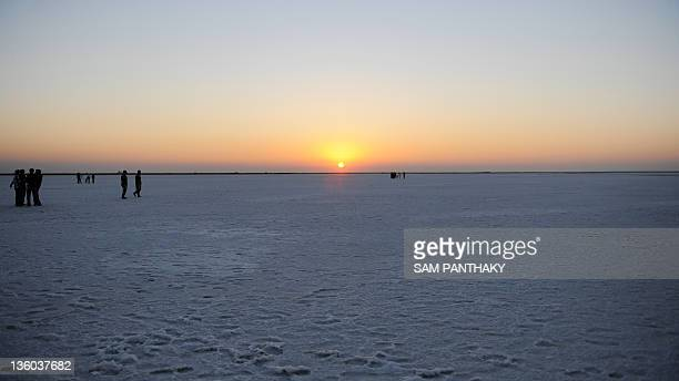 The evening sun sets over the 'White Desert' near Dhordo village close to the IndiaPakistan border some 500 kms from Ahmedabad on December 17 2011...