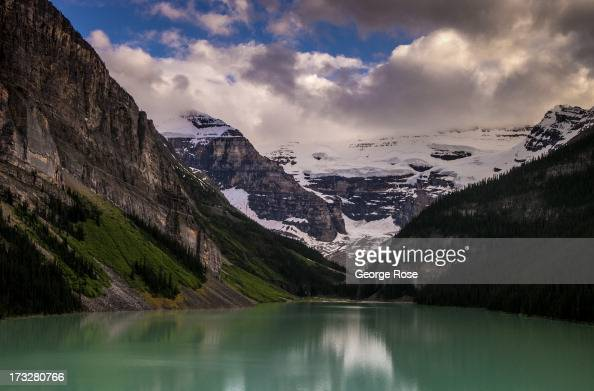 The everchanging weather conditions of Victoria Glacier and surrounding snowcapped mountains are reflected in the water of Lake Louise on June 26...