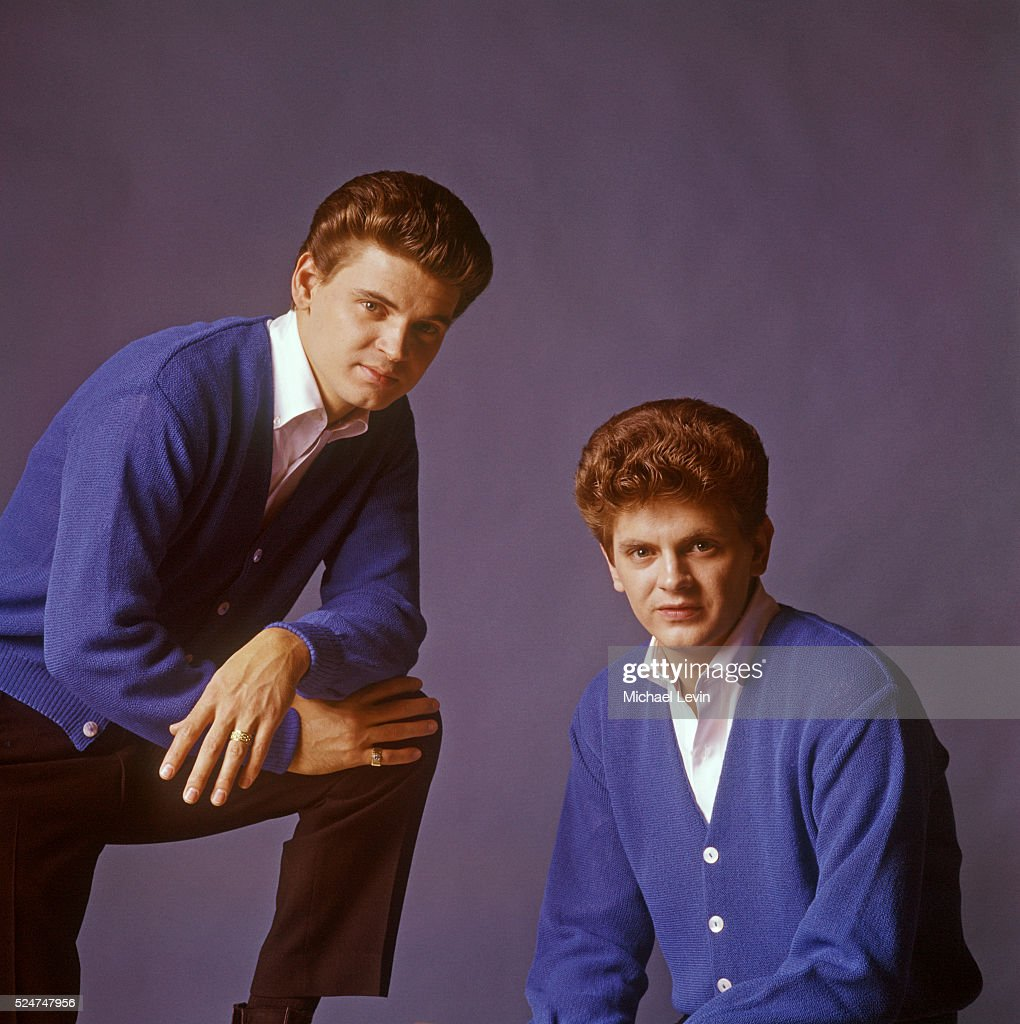 The Everly Brothers posing together in matching blue sweaters.