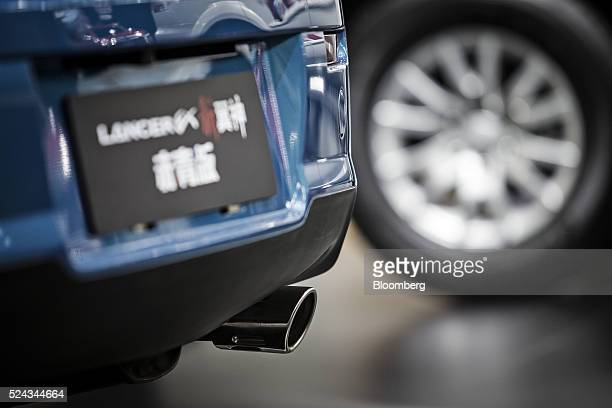 The exhaust pipe of a Mitsubishi Motors Corp Lancer EX vehicle is seen at the company's stand at the Beijing International Automotive Exhibition in...