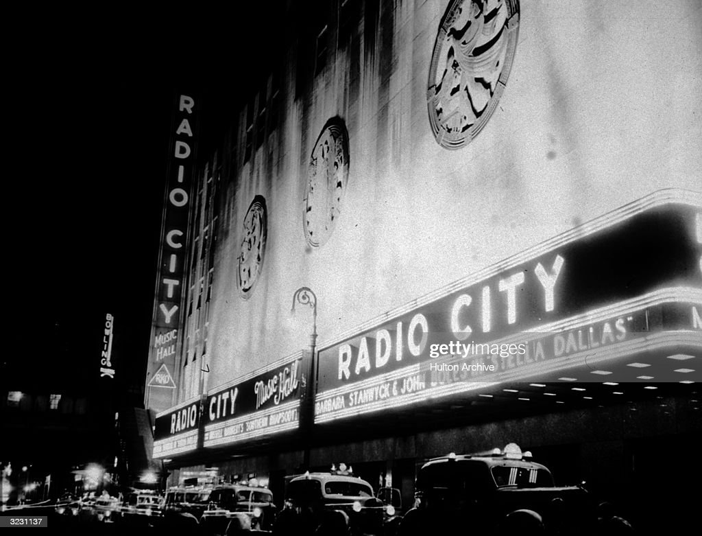 The exterior of Radio City Music Hall with a neon marquee advertising director King Vidor's film, 'Stella Dallas,' starring Barbara Stanwyck, Sixth Avenue, New York City. Automobiles and taxicabs are parked along the curb in front of the theater. The theater was designed by Samuel L Rothafel.