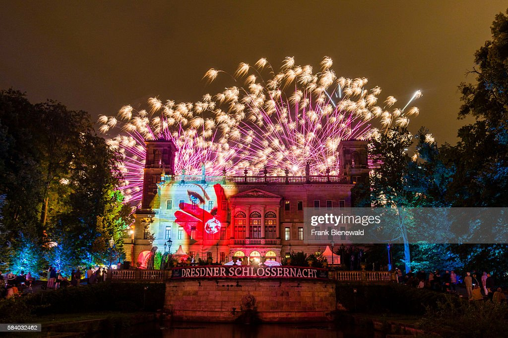 The facade of the castle Schloss Albrechtsberg is colorfully illuminated at the festival Schlössernacht at night fireworks are rising behind