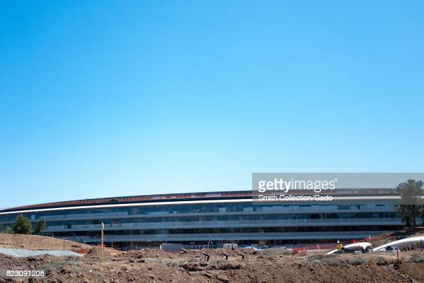 The facade of the main building is visible above a construction site at the Apple Park known colloquially as 'The Spaceship' the new headquarters of...