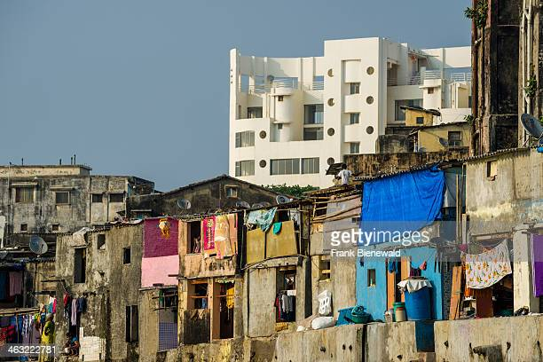 The facades of typical homes of poor working class Indians similar to the buildings in slum areas with a modern apartment building behind