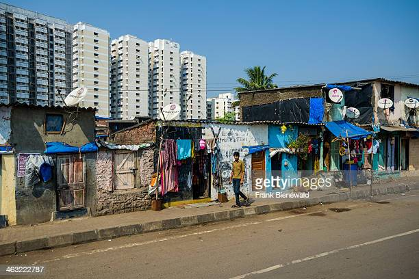 The facades of typical homes of poor working class Indians similar to the buildings in slum areas with modern apartment buildings behind