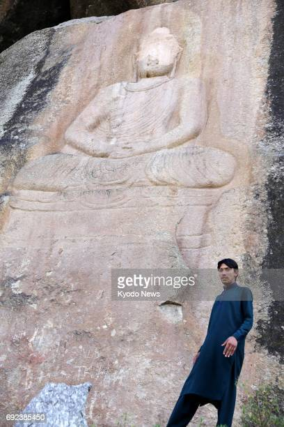 The face of a 6metertall Buddha rock sculpture disfigured after being vandalized by militants in 2007 is seen in this photo taken in November 2015 in...