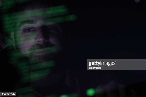 The face of an attendee is reflected in a laptop computer screen and overlaid with code as he participates in the TechCrunch Disrupt London 2015...