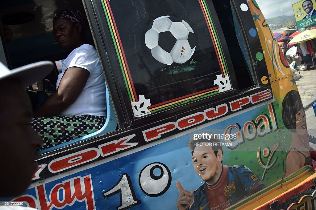 The face of Argentinian football player Lionel Messi is painted on a Tap Tap public transportation vehicle, in Port-au-Prince on May 27, 2016. Haiti will play Brazil, Ecuador, and Peru in the upcoming COPA America Centerario soccer tournament in the United States taking place between June 3 and June 26, 2016. / AFP / HECTOR