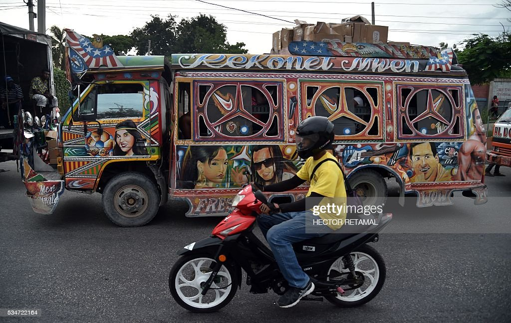 The face of Argentinian football player Lionel Messi (R) is seen painted on a Tap Tap public transportation vehicle, in Port-au-Prince on May 27, 2016. Haiti will play Brazil, Ecuador, and Peru in the upcoming COPA America Centerario soccer tournament in the United States taking place between June 3 and June 26, 2016. / AFP / HECTOR