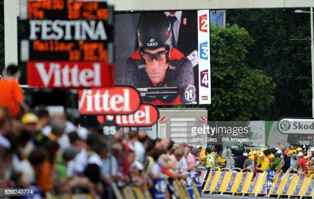 The face of Tour de France legend Lance Armstrong dominates the big screen above the crowds as he prepares to start his run during the Tour de France...