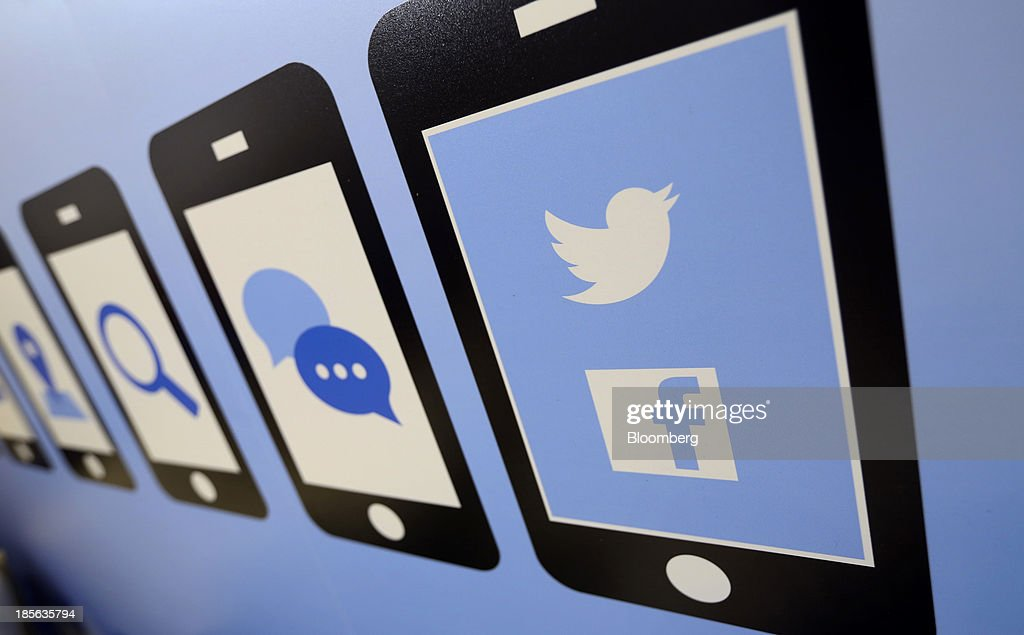The Facebook Inc. and Twitter Inc. company logos are seen on an advertising sign during the Apps World Multi-Platform Developer Show in London, U.K., on Wednesday, Oct. 23, 2013. Retail sales of Internet-connected wearable devices, including watches and eyeglasses, will reach $19 billion by 2018, compared with $1.4 billion this year, Juniper Research said in an Oct. 15 report. Photographer: Chris Ratcliffe/Bloomberg via Getty Images
