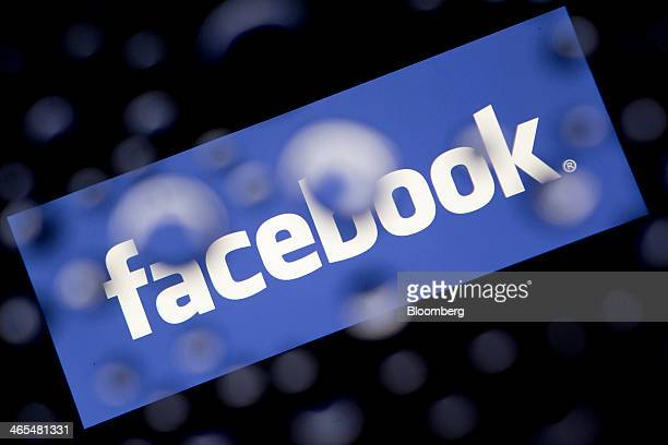 The Facebook Inc logo is displayed an Apple Inc iPad Air past water droplets in this arranged photograph in Washington DC US on Monday Jan 27 2014...