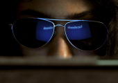 The 'Facebook' logo is reflected in a young Indian woman's sunglasses as she browses on a tablet in Bangalore on May 15 2012 World's popular and...