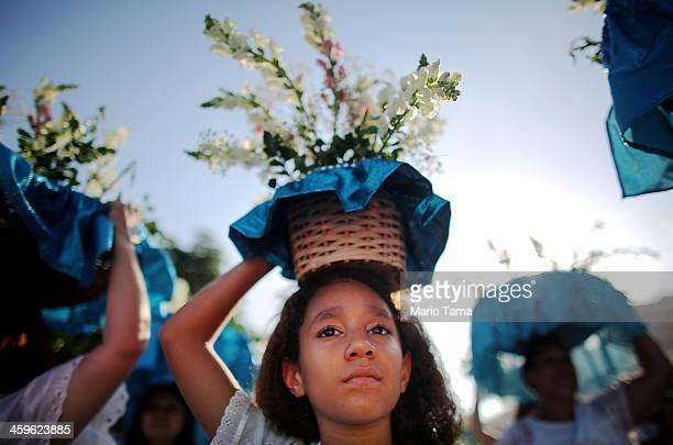The faithful carry offerings at a ceremony honoring Iemanja Goddess of the Sea as part of traditional New Year's celebrations on the sands of...