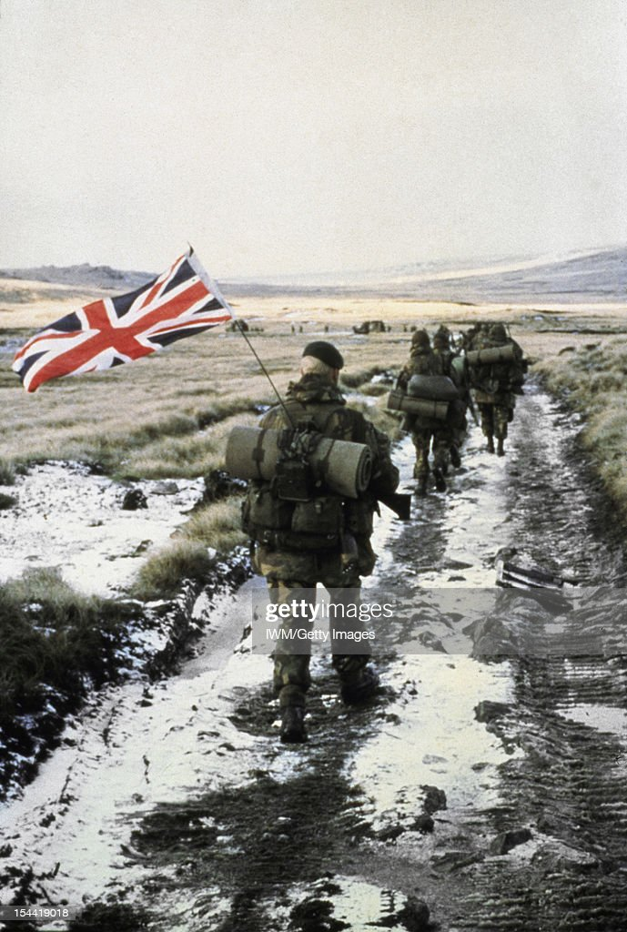 The Falklands Conflict, April - June 1982, Commandos from 40 Commando Anti-Tank Troop march towards Port Stanley in amongst a column of from 45 Commando (the unit to which they were attached). Royal Marine Peter Robinson, carrying the Union Flag attached to the aerial of the radio he is carrying, brings up the rear. The flag was owned by Marine John 'Snowy' Snowden who was unable to attach the flag to his backpack so he passed it to Robinson, circa 1982.