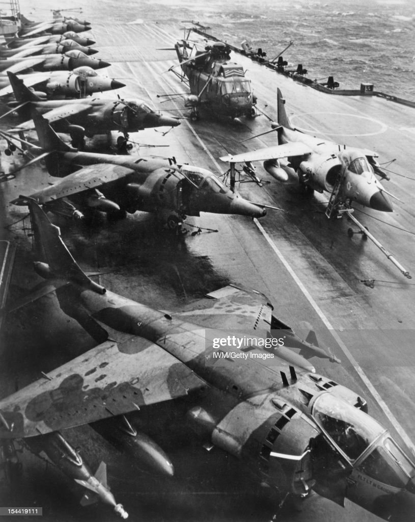 The Falklands Conflict, April - June 1982, Three Hawker Siddeley Harrier GR3s of No 1 Squadron RAF ranged (in the foreground) alongside seven Royal Navy British Aerospace Sea Harrier FR1s and a Sea King HAS.5 of 820 Naval Air Squadron on the flight deck of HMS HERMES, on the day that No 1 Squadron joined the ship in the South Atlantic. The first Harrier GR.3 is carrying a 1000lb laser-quided bomb (GBU-16 Paveway II) on its outer pylons. On the centre deck is Sea Harrier FRS.1 (XZ499) of 800 Naval Air Squadron, in which Lt Cdr Smith destroyed an Argentine Skyhawk.